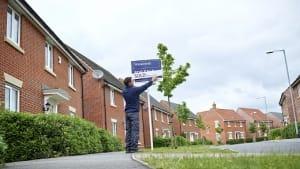 Man putting up an Estate Agency Board Man putting up an Estate Agency Board