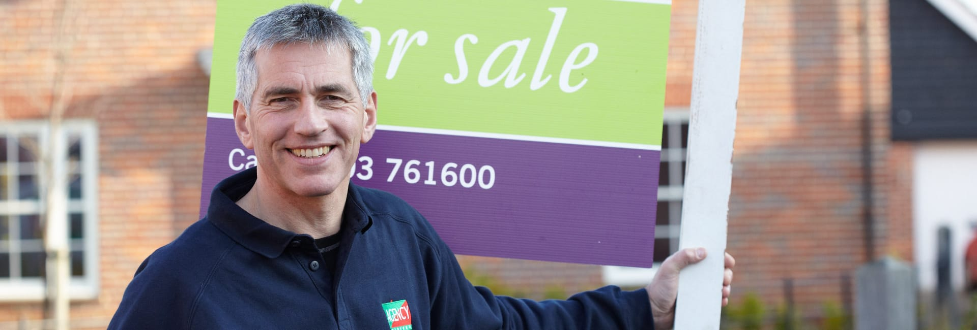 Agency Express franchisee success stories. Franchisee holding an estate agency for sale board.