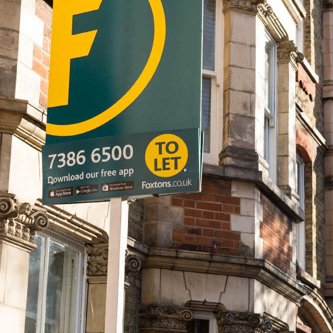 UK rental market - Estate agency board erected outside a row of houses