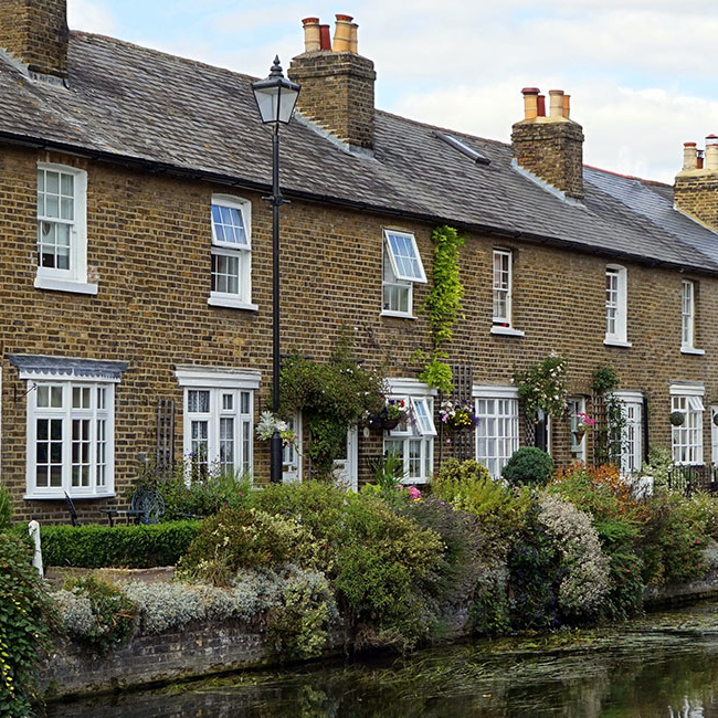 Row of country cottages next to a river - Property market - Property Activity