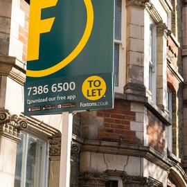 Green Foxtons lettings board outside a row of houses.